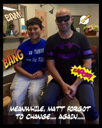 "Image is Cassius, sitting beside ""BatMatt"" [Matt, his ABA therapist, dressed as Batman] at the beginning of one of their many sessions. Photo caption says 'Meanwhile, Matt Forgot to Change...Again...'* Surrounded by comic-strip-like ""noise windows"" (Bam, Bang, KaPow!)"