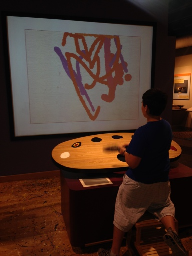 Image is of Cassius using an interactive digital display to create art. He said that his art was far better than many of the abstract paintings in the gallery. I agree with him.