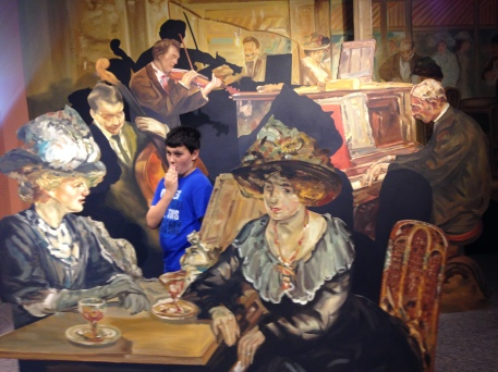 Image is of Cassius posed in a lifesized oil painting: he is standing beside the coffee table with two women drinking (presumably tea), while a violinist plays in the background. His facial expression is hilarious, his hand is over his mouth as if he has just heard some truly *dirty* gossip.