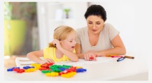 Image is a young blond little girl sitting with her Behavioral Analysis at a table playing with blocks, actively engaging in the positive-reinforcement-based therapy known as ABA, or Applied Behavior Analysis.