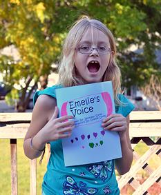 Image is an excited Emelie, holding her newly published book Emelie's Voice, available both in print and for download from Amazon.com