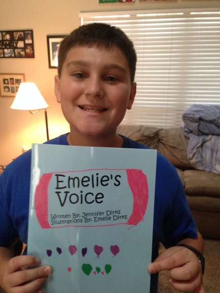 "Image is Cassius holding his copy of ""Emelie's Voice,"" a book written by Emelie and her mother, Jennifer Dirks."